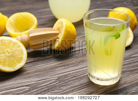 Delicious lemon juice in glass on wooden background