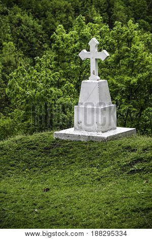 white cross on a hillock on the edge of the forest