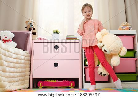 Cute little girl with a big teddy bear play in the children's room