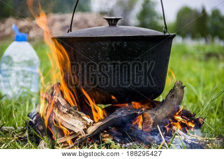 close-up of black cauldron on the campfire