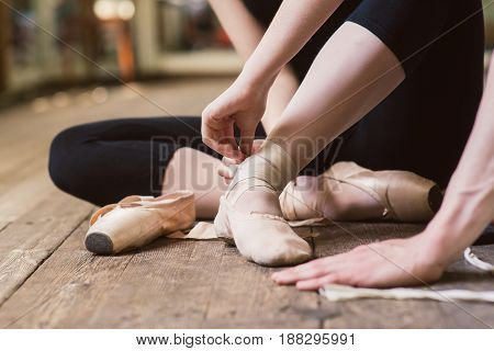 Young ballerina or dancer girl putting on her ballet shoes on the wooden floor. Ballet dancer tying ballet shoes. close-up.