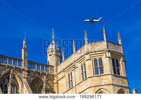 Windsor England - 9 April 2017 - British Airways commercial aircraft flies above Windsor Castle on a clear blue sky day at Windsor England on April 9 2017