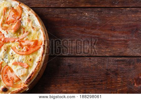 Baked appetizing pizza with cheese, tomato and salmon, flat lay. Italian fast food served on wooden rustic table, free space for text.