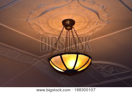 old vintage iron light fixture hanging from art deco decorative ceiling with warm light
