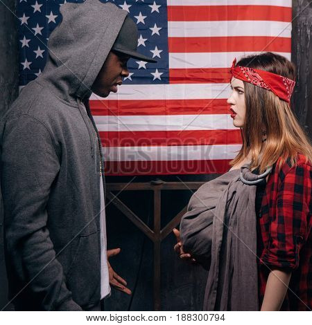 Divorce in american family. Quarrel with wife. Black man and caucasian woman with little baby on US national flag background. Social problem, child custody, youth pregnancy concept