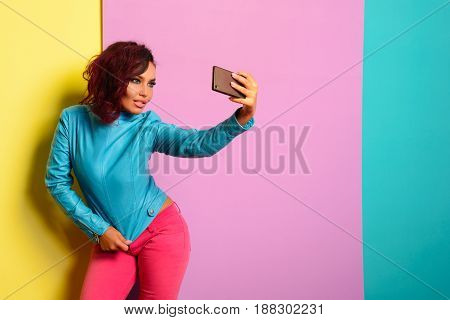 Fashion pretty woman makes self portrait on smartphone in blue jacket over Tricolor background