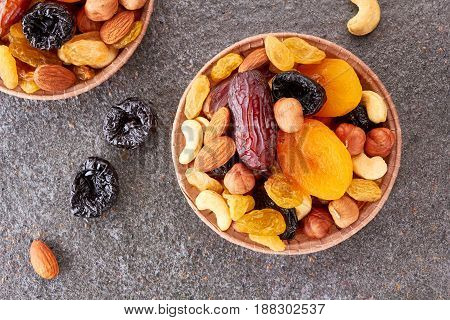 Paper forms with mix of dried fruits and nuts over stone background. Top view