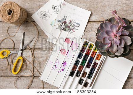 Sketch of bouquet. Decorator workshop, tools top view. Florist workplace with decor. Decorative creative artwork , paint, succulent