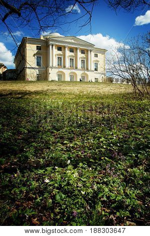 A beautiful old mansion stands on a hill in the park, in the foreground flowered flowers.