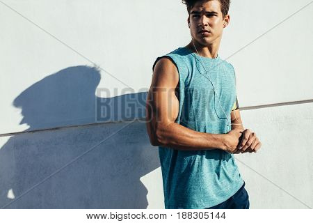 Shot of muscular young man relaxing after workout. Male runner man taking a break from running training.