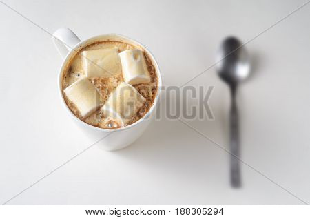 Cup Of Coffee with Marshmallow. Top view of white mug of hot drink with blury spoon background