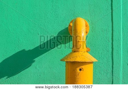 Green plaster wall with yellow pipe. Drop swhadow background