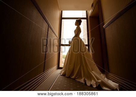 beautiful silhouette portrait of young blonde bride in wedding dress