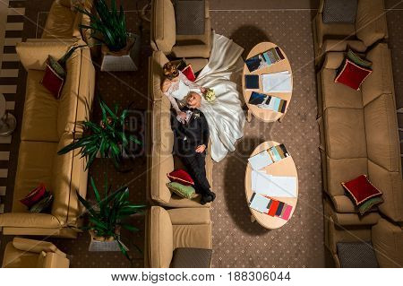 young just merried couple lying on the sofa at home