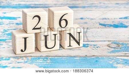June 26th. Wooden cubes with date of 26 June on old blue wooden background.