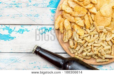 Beer bottle with salty snacks on the old table. Top view.