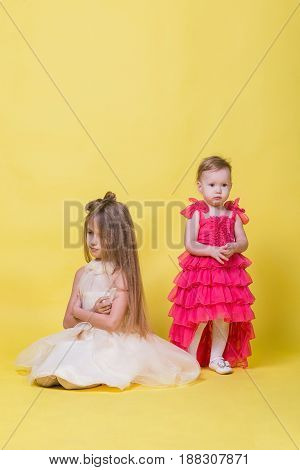 Two sisters in dresses on a yellow background look in different directions and offended.