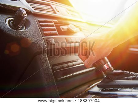 A man's hand on an automatic gearbox. Automatic shift transmission close up. Sunlight.