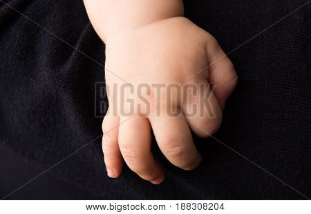 bare hand of baby clinging on dark sweater