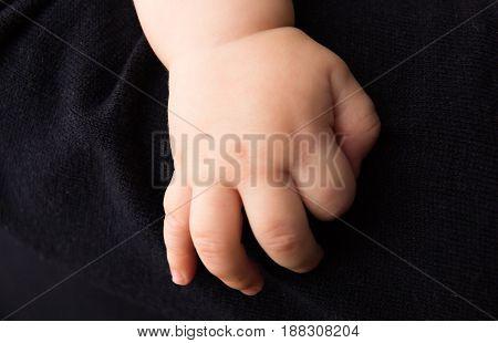 bare hand of baby clinging on dark sweater