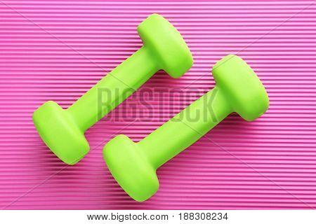 Green dumbbells on pink background, close up