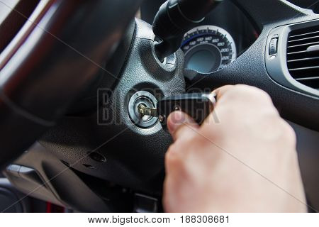 Close-up Of Person's Hand Inserting Key To Start Car