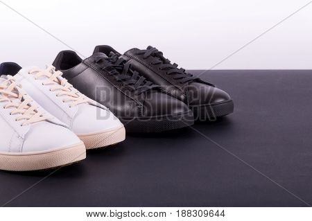 Two pair of sneakers shoes on black background. Black and white shoe