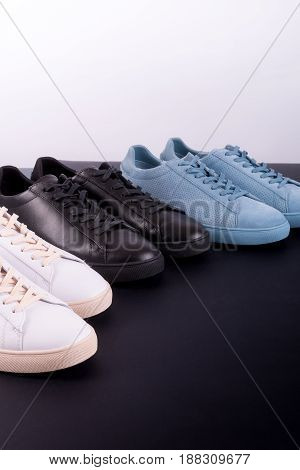 Three pair of sneakers on black background. Black, white and blue shoe