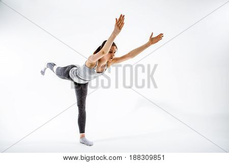 Young brunette stretching on clean white background