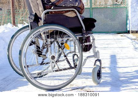 Adult Man In Wheelchair. Close Up Photo Of Male Hand On Wheel