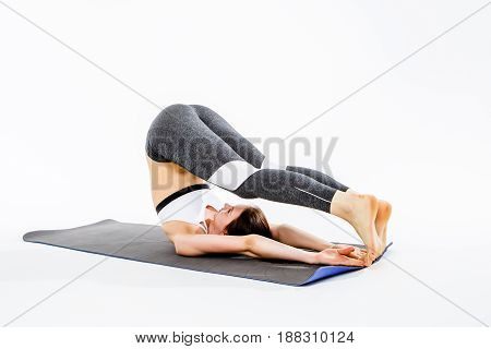 Girl doing stretching on rug at isolated background