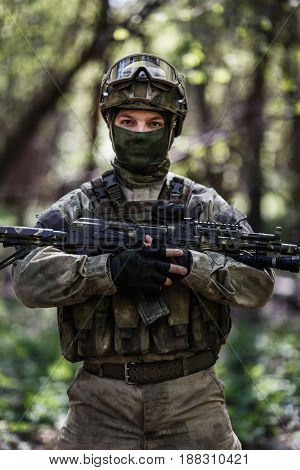 Soldier with submachine gun patrols forest during day