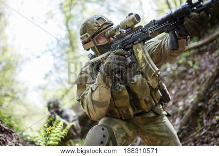 Photo of sighted soldier with gun in woods during day