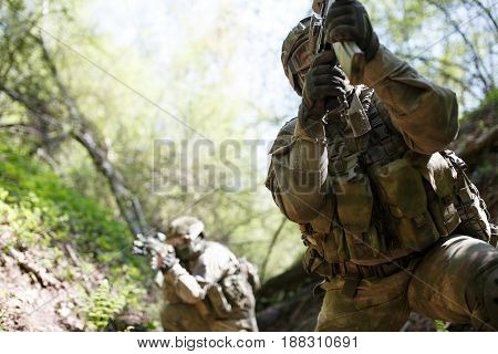 Officers on military mission in woods during day