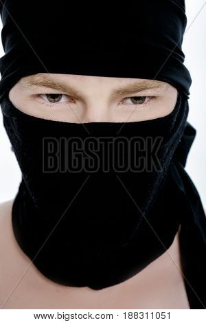Portrait of a ninja man in a black mask on a white background