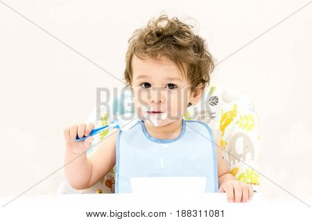 Cute Toddler Boy With Blue Spoon Is Yogurt. The Child Smiles. Funny Kid In A Baby Seat. Beautiful 2