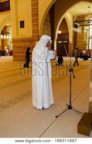 Manama Bahrain - July 9 2016: Arab Muezzin standing in the Al Fateh Grand Mosque leading prayer.