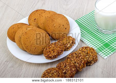 The composition of biscuits and a glass jar with yogurt. Cookies and milk white yogurt, on a white background with reflection. Tasty yellow brown cookies. Yogurt and oatmeal cookies.