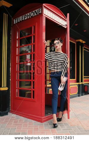 Beautiful Girl With Dark Hair Walking By The Street, Red Phone Booth On Background