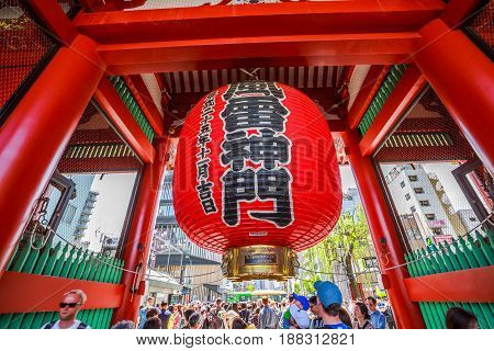 Tokyo, Japan - April 19, 2017: famous giant red lantern Kaminarimon Gate of Senso-ji Temple in Asakusa area. The Japanese word on the lantern means THUNDER GATE. Crowd of tourists on background.