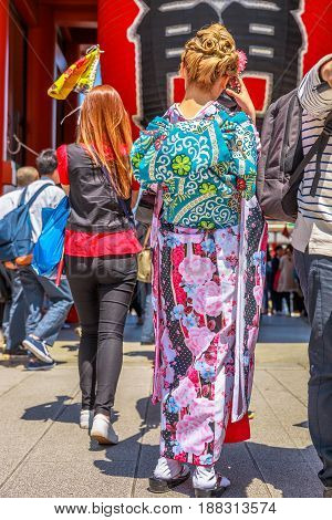 Tokyo, Japan - April 19, 2017: woman's back in japanese kimonos taking photo of giant red lantern. Kaminarimon Gate in Senso-ji Temple, Asakusa. The Japanese word on the lantern means THUNDER GATE.