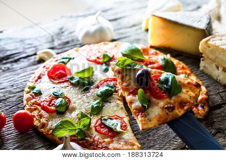 Pizza on wood with ingredients. Pizza with cheese tomatoes and basil. Rustic italian pizza