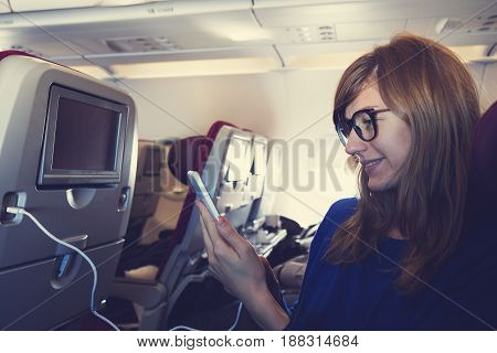 Girl using cellphone and touchscreen in the airplane.