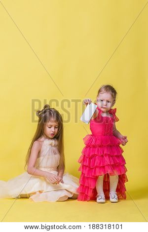 Two sisters in dresses on a yellow background and a mobile smartphone.
