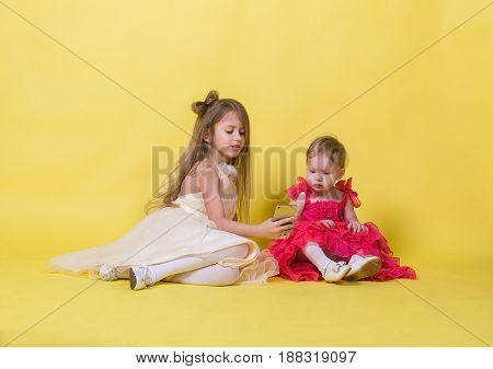 Two sisters in dresses on a yellow background photographed themselves on the phone.