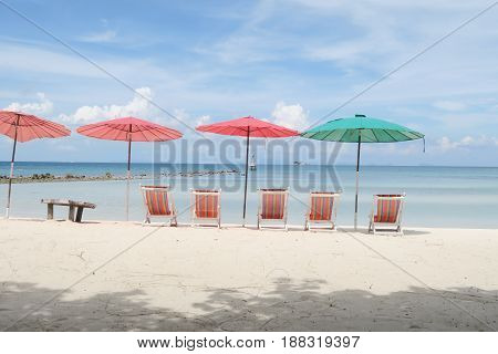 Sun umbrella and beach beds on tropical coastline in Thailand