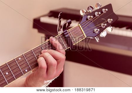 Man's hand plays the guitar with piano on a background