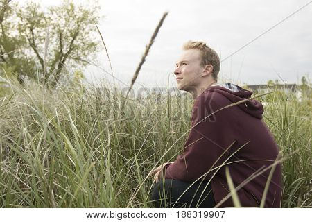 Cool young adult looking up in field