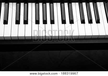 Piano with white and black piano keys on a dark background