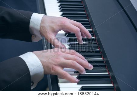man's hands in a black jacket playing on a piano at the concert
